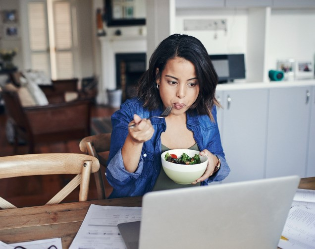 Woman sitting at computer eating a salad while working