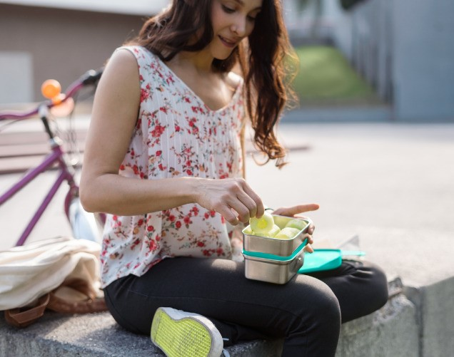 Woman sitting outside in courtyard eating a healthy snack of cucumber slices