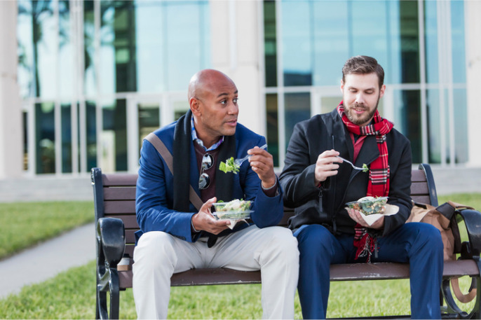 Two men eating lunch on bench outside office building